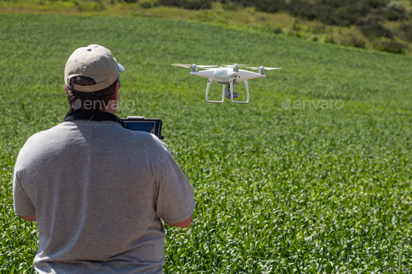 UAV Drone Pilot Flying and Gathering Data Over Country Farm Land - Stock Photo - Images