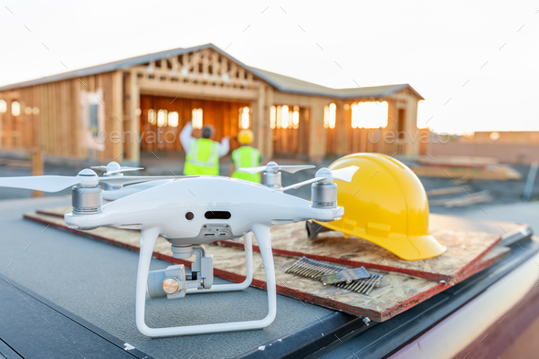 Drone Quadcopter Next to Hard Hat Helmet At Construction Site with Workers Behind - Stock Photo - Images