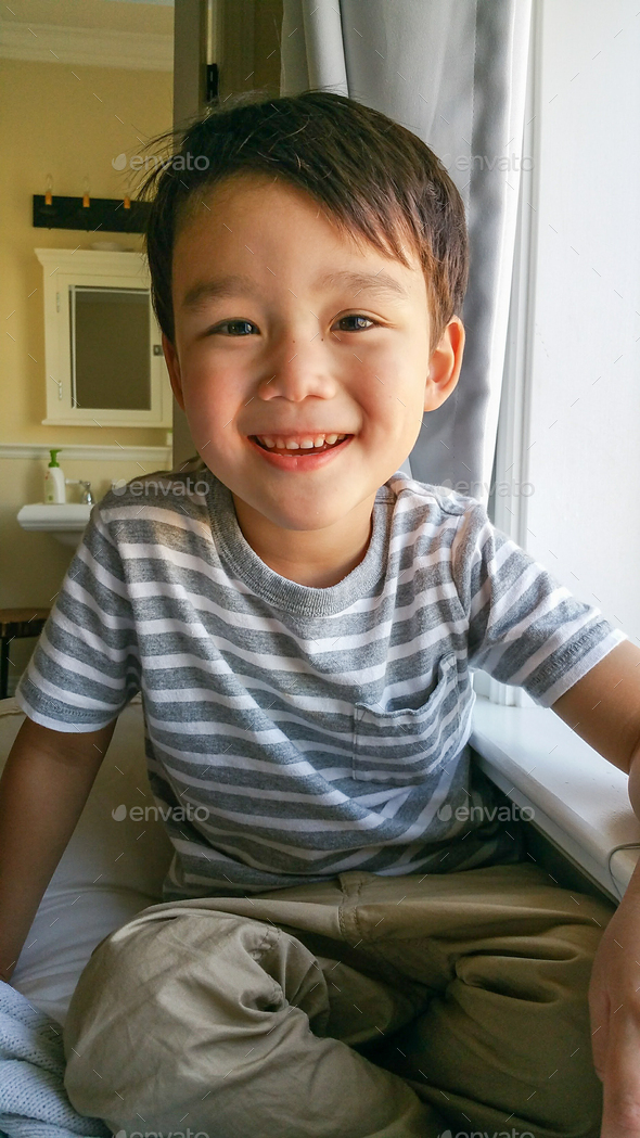 Happy Cute Young Chinese and Caucasian Boy Sitting Near Window - Stock Photo - Images