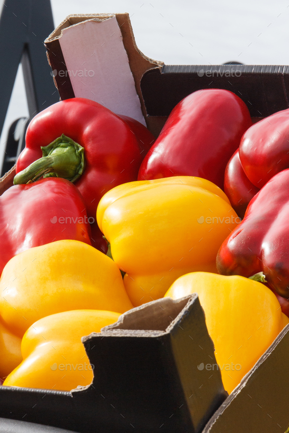 Fresh ripe red and yellow peppers in box on stall at bazaar - Stock Photo - Images