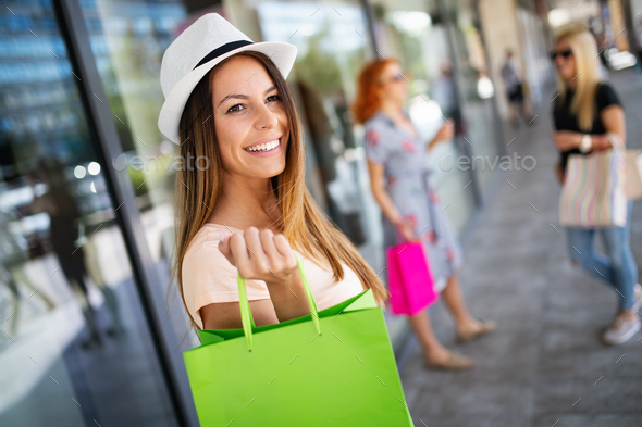 Shopping, fun and tourism concept. Beautiful girls with shopping bags in ctiy - Stock Photo - Images