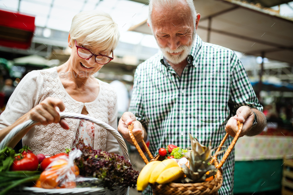 Smiling senior couple holding basket with vegetables at the market - Stock Photo - Images