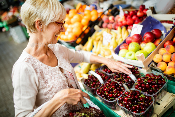 Only the best fruits and vegetables. Beautiful mature woman buying fresh food on market - Stock Photo - Images