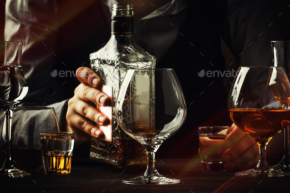 The bartender pours the cognac or brandy - Stock Photo - Images