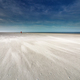 lone man walking on sand beach by North sea - PhotoDune Item for Sale