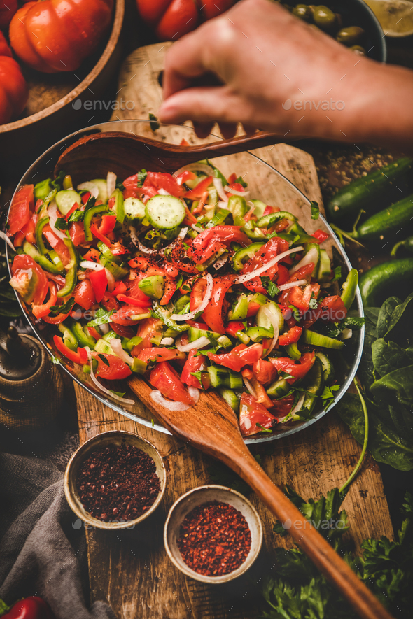 Womans hands adding spices to Turkish Chopard Salad with vegetables - Stock Photo - Images