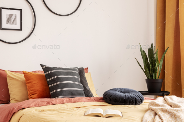 Black round velvet pillow on yellow duvet in trendy bedroom interior with king size bed - Stock Photo - Images