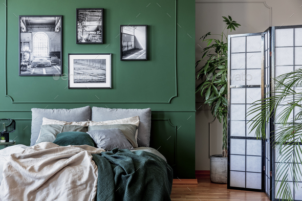 Gallery of black and white posters and photos on emerald green wall in trendy bedroom - Stock Photo - Images