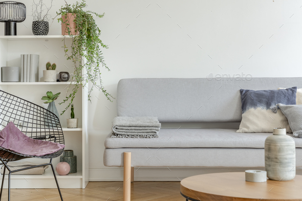 Bookshelf with knick knacks next to comfortable grey sofa in chic living room - Stock Photo - Images