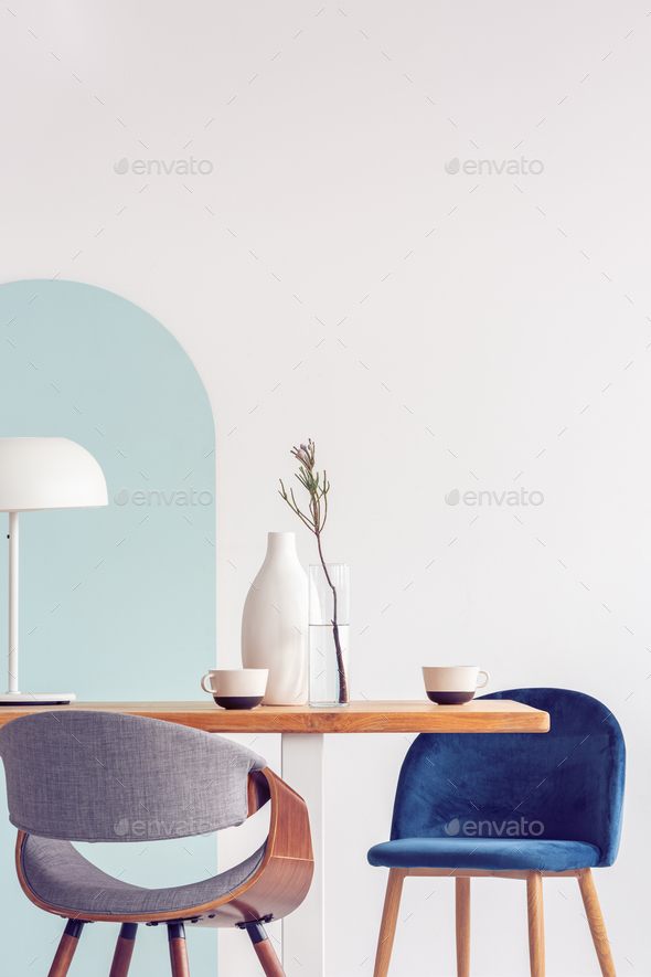 Stylish pastel pink and petrol blue chairs at long wooden table in bright dining room - Stock Photo - Images
