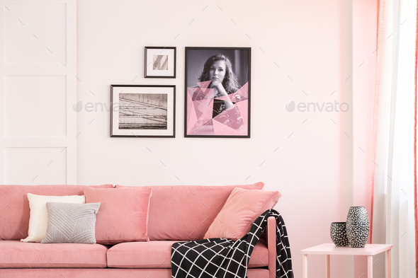 Gallery of posters on empty white wall of bright living room interior with pastel pink settee - Stock Photo - Images
