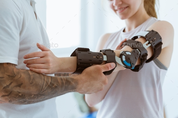 Tattooed physiotherapist who puts an orthosis on the hand of a young patient after an accident - Stock Photo - Images