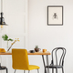 Stylish yellow chair at wooden dining table in trendy interior - PhotoDune Item for Sale