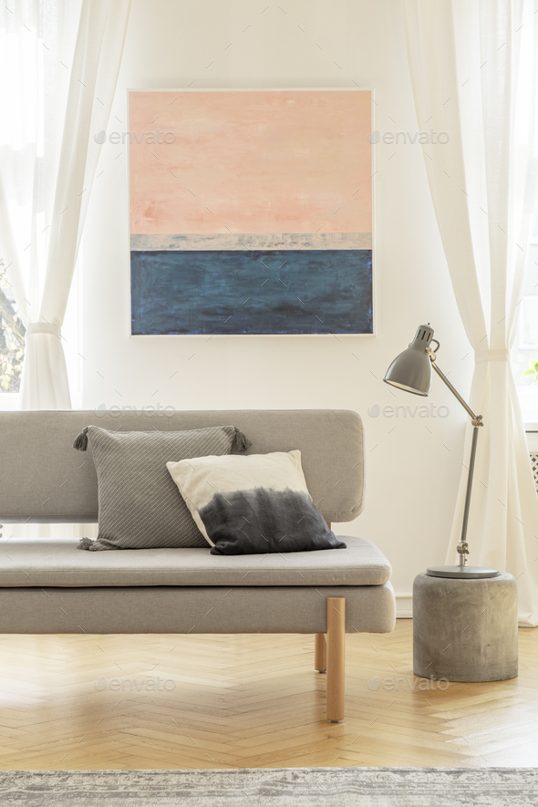 Grey lamp on small table next to comfortable sofa with pillows - Stock Photo - Images