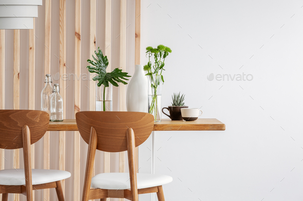 Green plants in small vases on long wooden dining table in bright interior - Stock Photo - Images