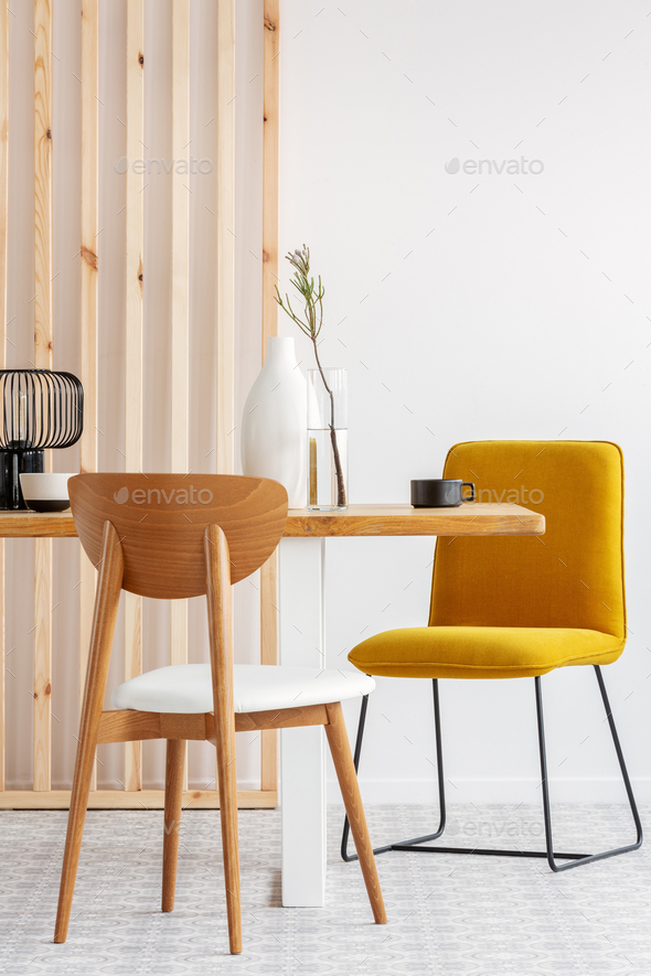 Stylish yellow chair at wooden dining table in trendy interior - Stock Photo - Images