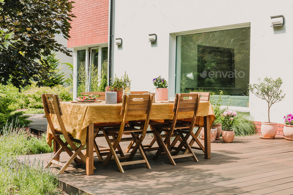 Dining table covered with orange tablecloth standing on wooden terrace in green garden - Stock Photo - Images