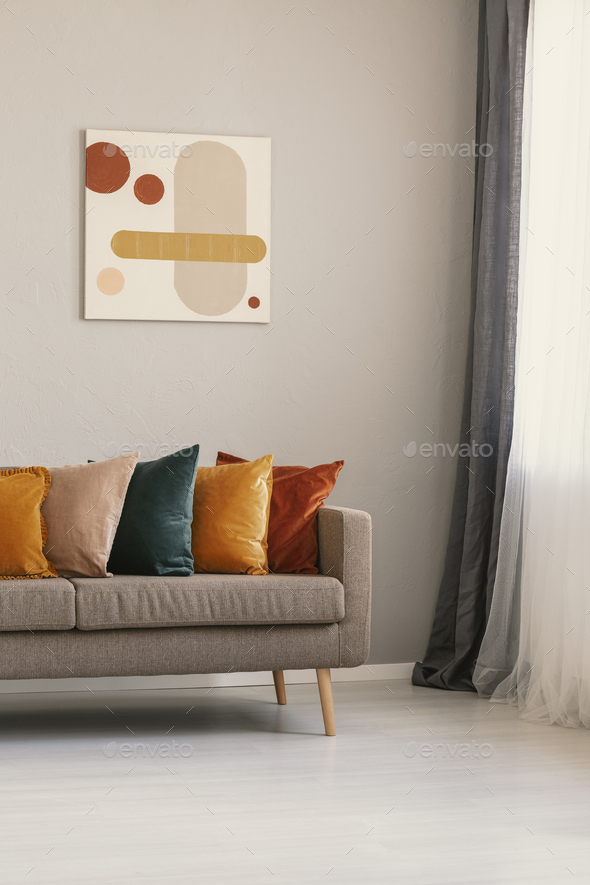 Abstract painting on beige wall above brown sofa with colorful pillows - Stock Photo - Images