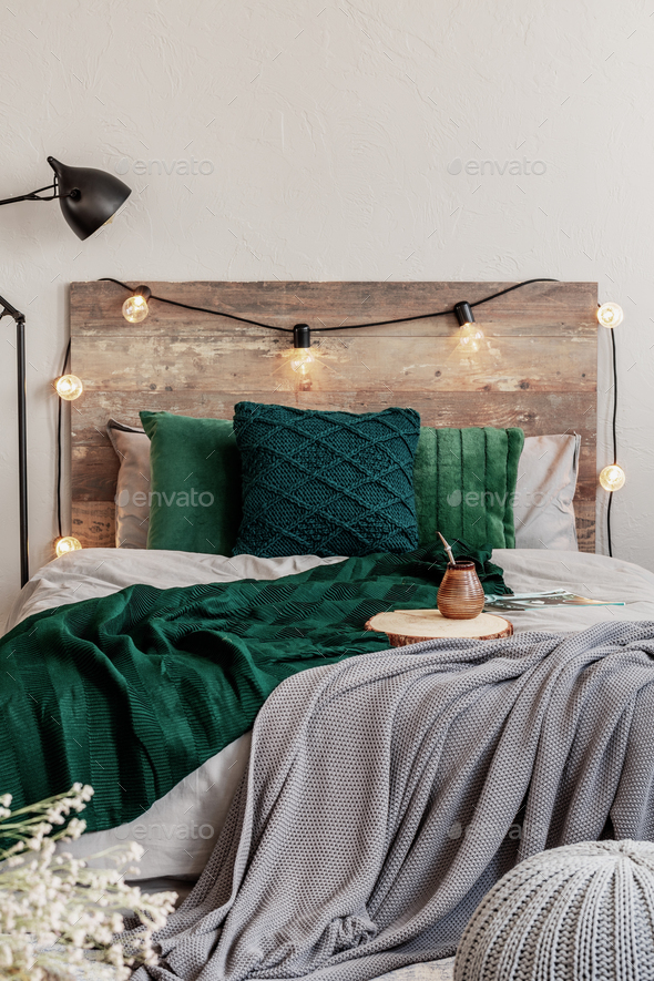 Emerald green pillows and blanket on wooden king size bed with grey bedding - Stock Photo - Images