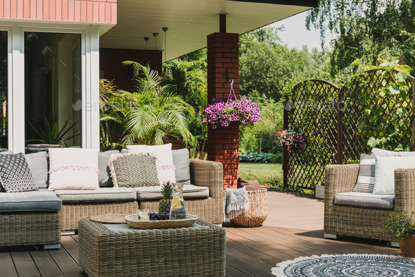 Classy furniture on wooden terrace in green beautiful garden - Stock Photo - Images