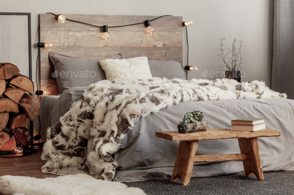 Wooden bench in the foot of the bed with grey bedding and cozy blanket - Stock Photo - Images
