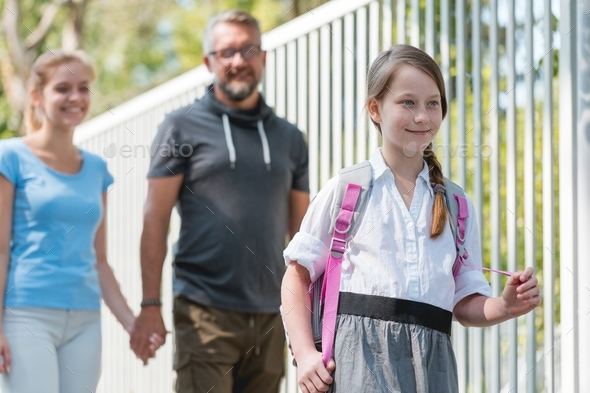 Girl walking with parents - Stock Photo - Images