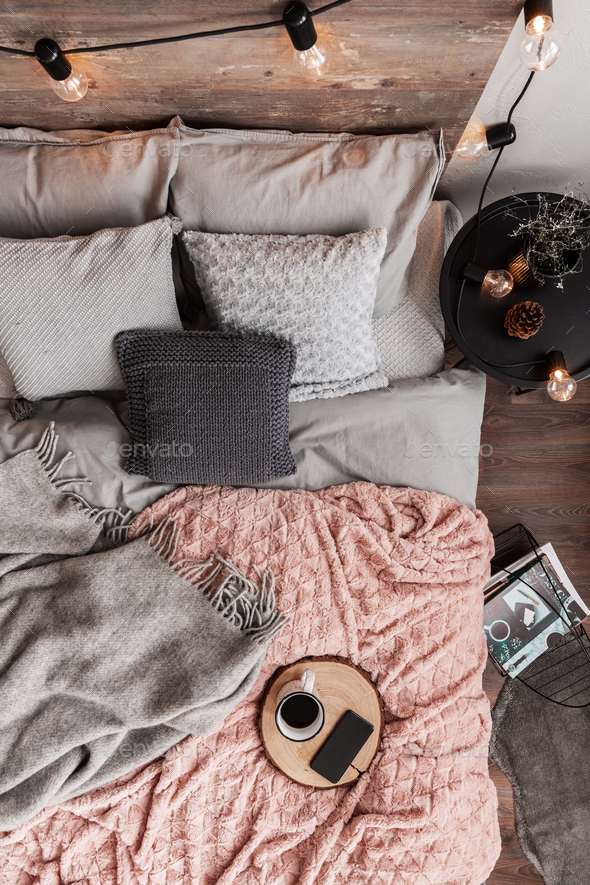 Top view of cozy king size bed with grey bedding and pastel pink blanket - Stock Photo - Images