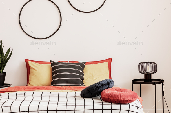 Black hoops on a white wall in an elegant bedroom with orange bedding on the bed - Stock Photo - Images