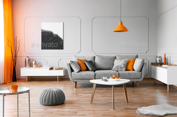 Stylish coffee table with kinck knacks in front of elegant couch with pillows - Stock Photo - Images