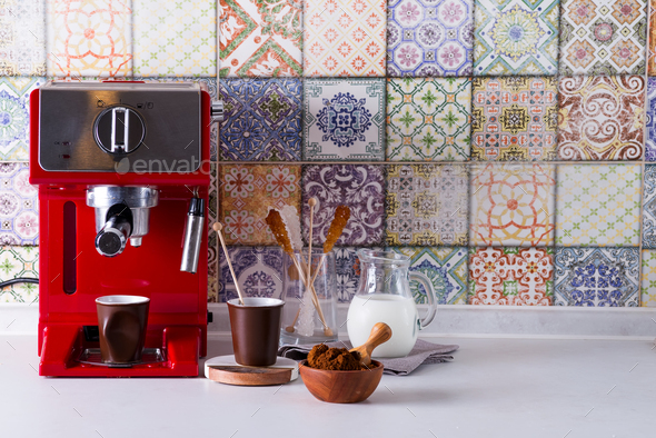 Home espresso machine on kitchen countertop with two cups, milk and sugar on sticks. Making coffee - Stock Photo - Images