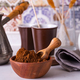 Grinded coffee in a wooden bowl with brown sugar stick on the background of a copper turks - PhotoDune Item for Sale
