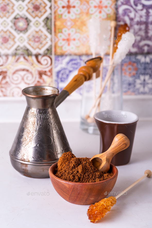 Grinded coffee in a wooden bowl with brown sugar stick on the background of a copper turks - Stock Photo - Images