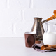 Jug of milk and ground coffee for making a drink at home on a stone countertop against a white - PhotoDune Item for Sale