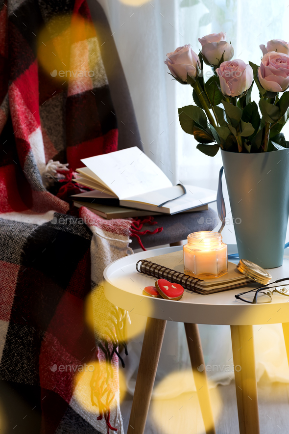 A candle with a notebook on a table with pink roses in a box near a window with a chair, a plaid and - Stock Photo - Images