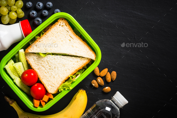 Lunch box with sandwich and fruits on black - Stock Photo - Images