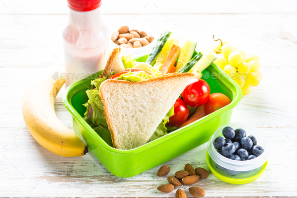 Lunch box with sandwich, vegetables, berries and nuts - Stock Photo - Images