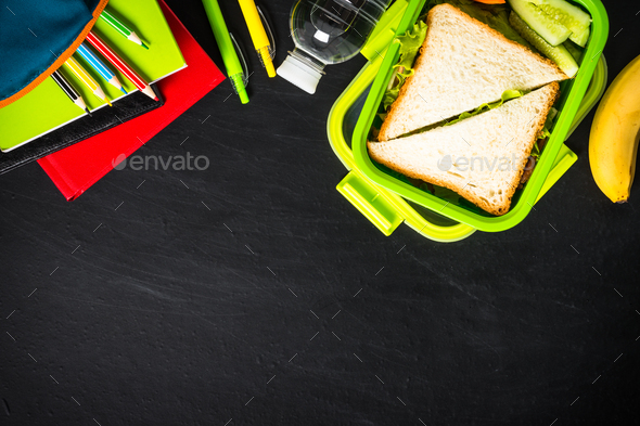 Back to school concept. Lunch box with stationery on black - Stock Photo - Images