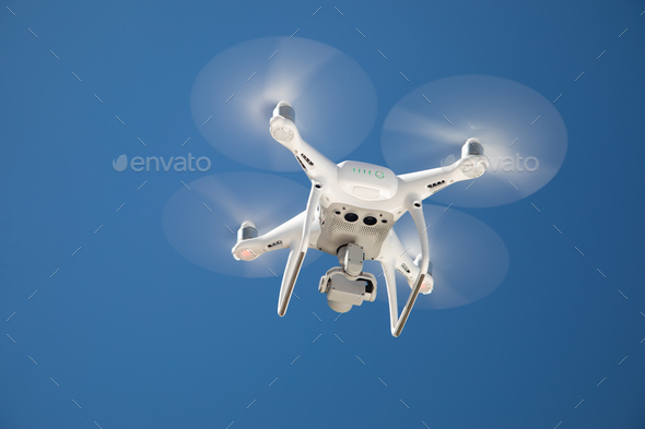Drone Quadcopter From Below Against A Blue Sky - Stock Photo - Images