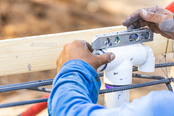 Plumber Using Level While Installing PVC Pipe At Construction Site - Stock Photo - Images