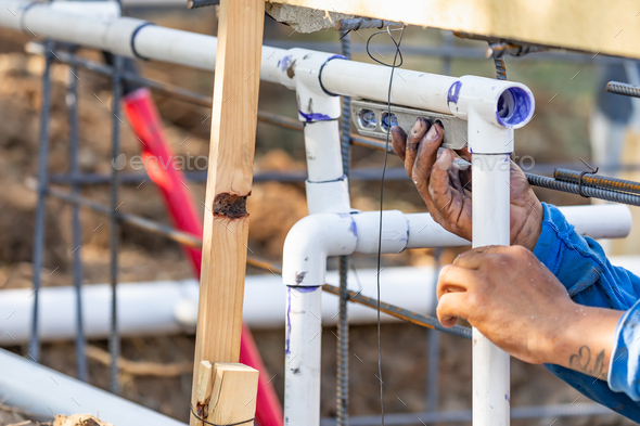 Plumber Using Level While Installing PVC Pipe At Construction Site. - Stock Photo - Images