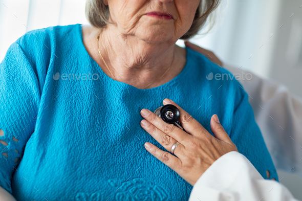 Female Doctor Checking The Heart With Stethoscope of Senior Adult Woman - Stock Photo - Images