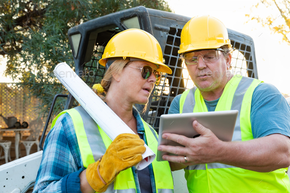 Male and Female Workers With Technical Blueprints and Computer Tablet Talking at Construction Site - Stock Photo - Images