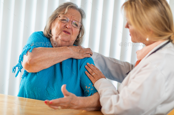 Senior Adult Woman Talking with Female Doctor About Sore Shoulder - Stock Photo - Images