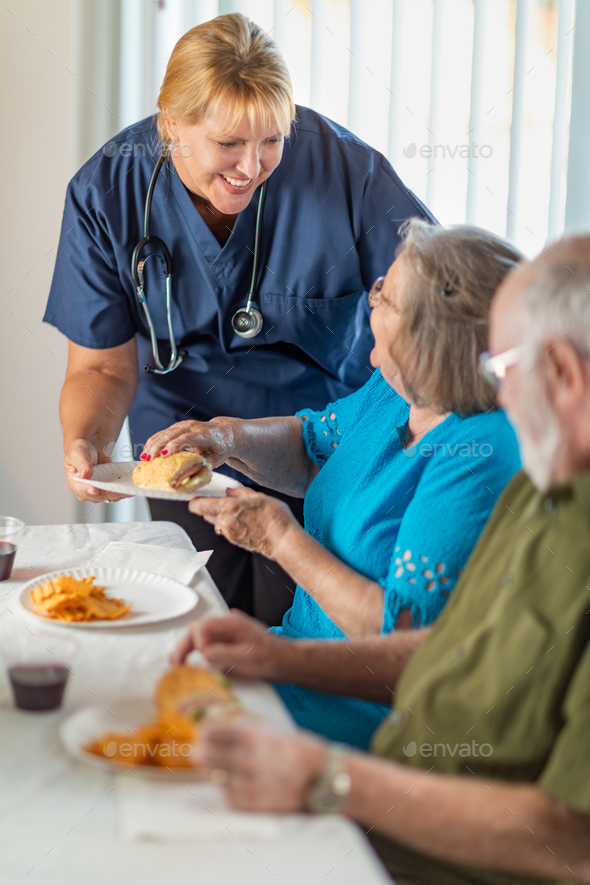 Female Doctor or Nurse Serving Senior Adult Couple Sandwiches at Table - Stock Photo - Images