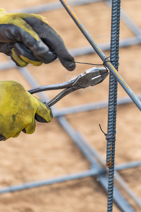 Worker Securing Steel Rebar Framing With Wire Plier Cutter Tool At Construction Site - Stock Photo - Images