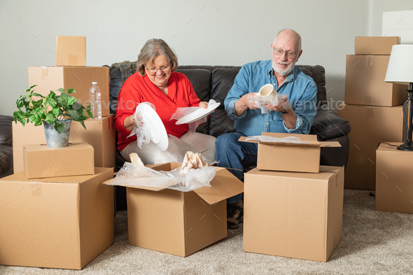 Senior Adult Couple Packing or Unpacking Moving Boxes - Stock Photo - Images