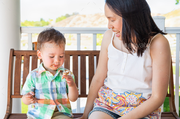 Chinese Mother Sitting With Her Mixed Race Chinese and Caucasian Boy Enjoying His Ice Cream Cone - Stock Photo - Images
