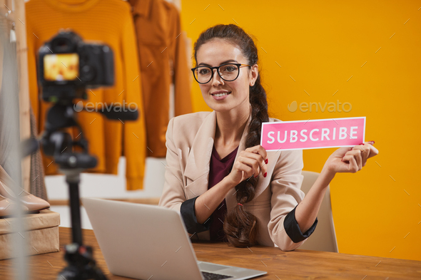 Smiling Young Woman Holding Subscribe Button - Stock Photo - Images