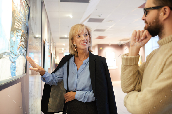 Smiling Woman Pointing at Painting in Art Gallery - Stock Photo - Images