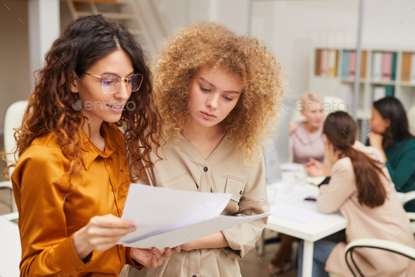 Two Female Office Workers Reading Documents - Stock Photo - Images